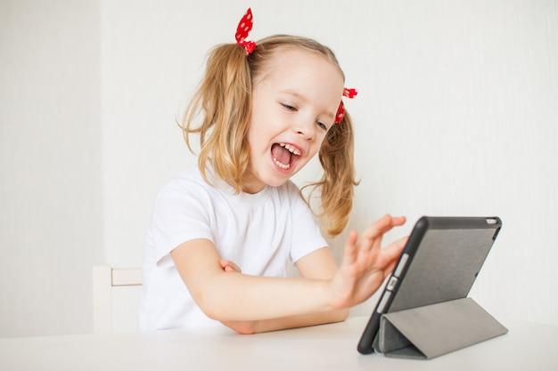 La bambina sta parlando online. scuola a casa