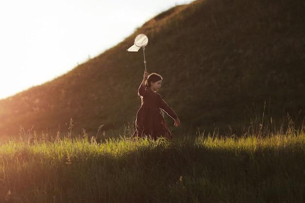 La bambina sta camminando con il retino per farfalle e sta catturando le farfalle sulle verdi colline in una soleggiata giornata estiva. copia spazio.