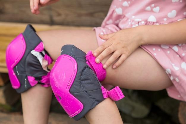 Una bambina indossa una protezione per il pattinaggio a rotelle seduto sui gradini della sua casa di campagna il concetto di uno stile di vita sano e attivo e di una guida sicura