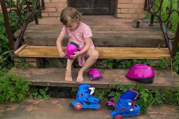 Una bambina indossa una protezione per il pattinaggio a rotelle seduta sui gradini della sua casa di campagna