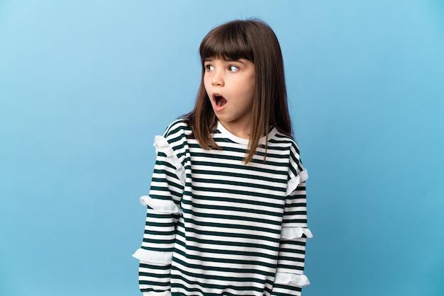 Bambina su sfondo isolato che fa un gesto di sorpresa mentre guarda di lato