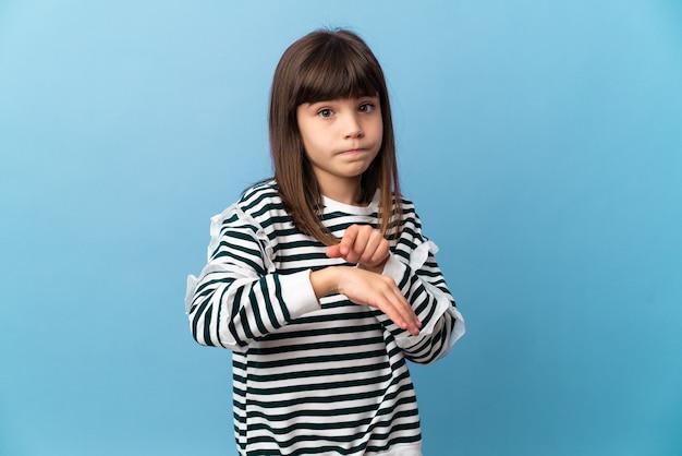 Bambina su sfondo isolato facendo il gesto di essere in ritardo