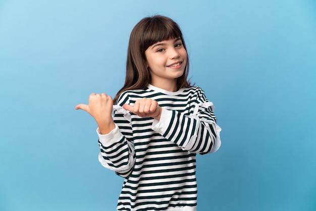 Bambina su sfondo isolato che punta al lato per presentare un prodotto