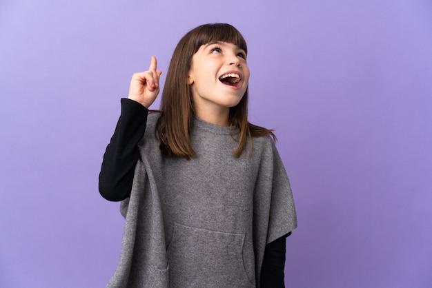 Bambina su sfondo isolato rivolto verso l'alto e sorpresa