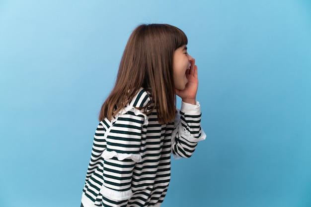 Bambina su sfondo isolato che grida con la bocca spalancata di lato