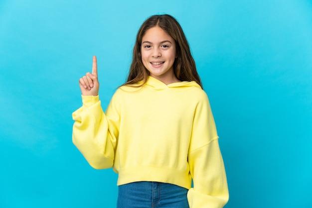 Bambina su sfondo blu isolato che indica una grande idea
