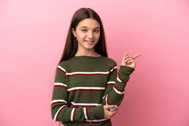 Bambina su sfondo rosa isolato felice e rivolta verso l'alto