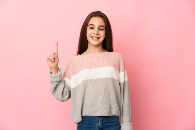Bambina isolata su sfondo rosa che indica una grande idea