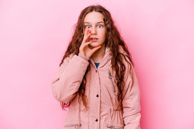 La bambina isolata sulla parete rosa sta dicendo una notizia segreta di frenata calda e sta guardando da parte
