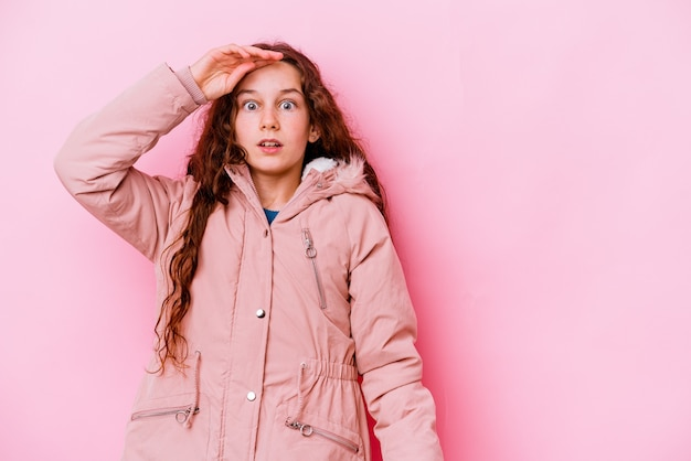 Bambina isolata sulla parete rosa che guarda lontano tenendo la mano sulla fronte
