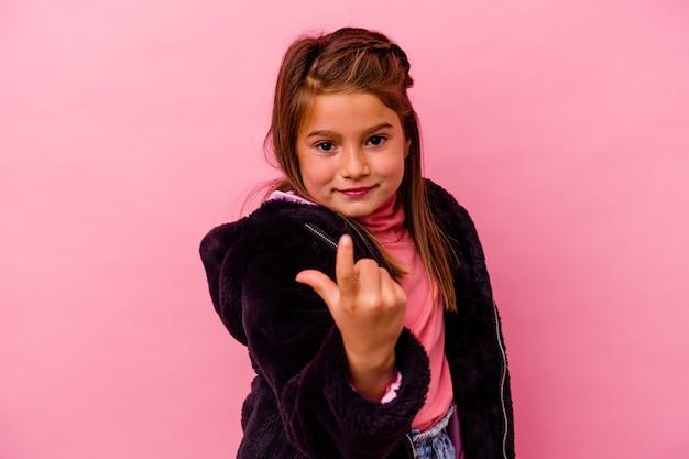 Bambina isolata sul muro rosa che punta il dito contro di te come se invitando ad avvicinarsi