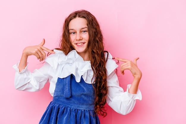 La bambina isolata sulla parete rosa punta verso il basso con le dita, sensazione positiva