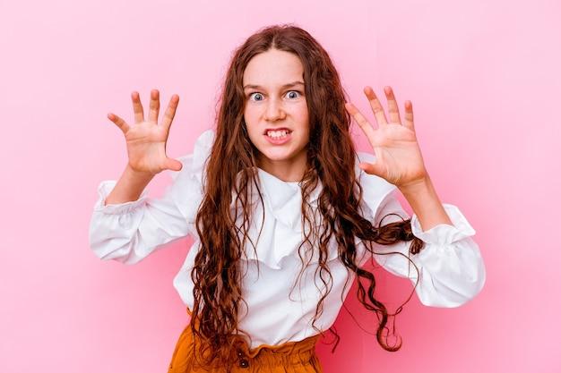 Bambina isolata sulla parete rosa che mostra gli artigli che imitano un gatto, gesto aggressivo