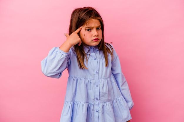 Bambina isolata sulla parete rosa che mostra un gesto di delusione con l'indice