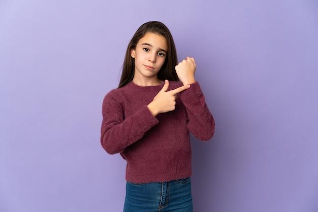 Bambina isolata su sfondo viola che fa il gesto di essere in ritardo