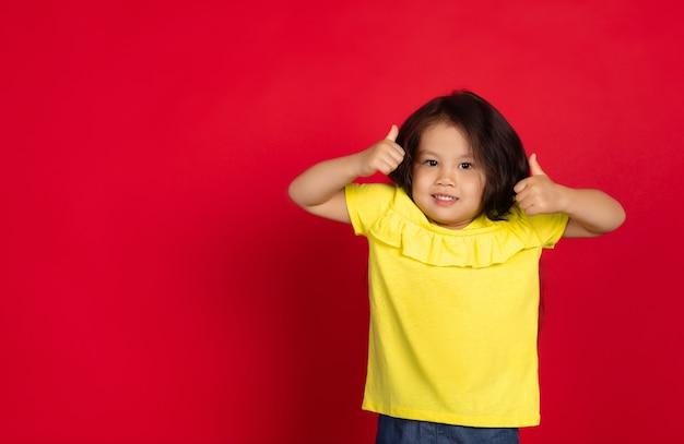 Bambina isolata su sfondo rosso