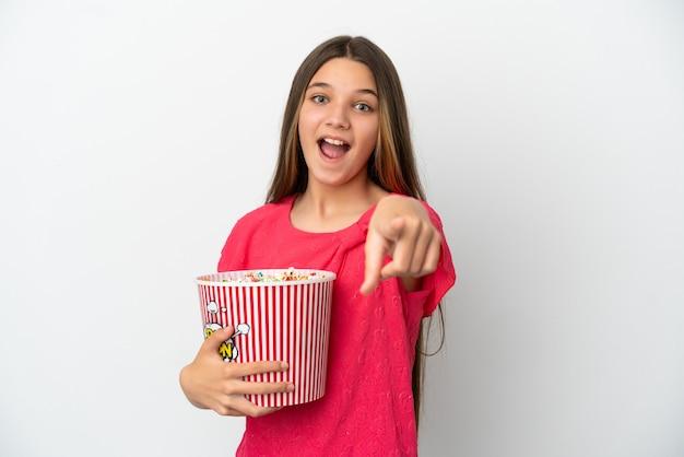 Bambina sopra fondo bianco isolato che tiene un grande secchio di popcorn mentre indica la parte anteriore