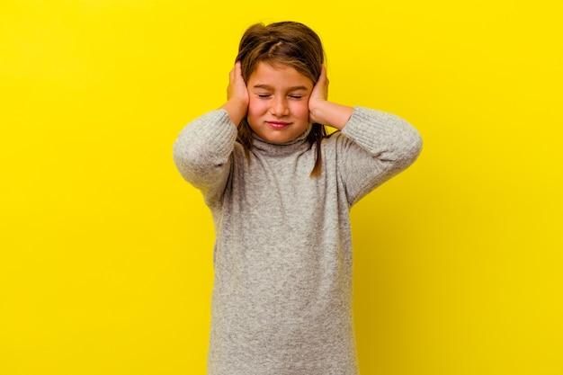Bambina isolata sul muro giallo che copre le orecchie con le mani
