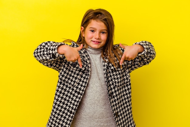 La bambina isolata sulla parete gialla punta verso il basso con le dita, sensazione positiva