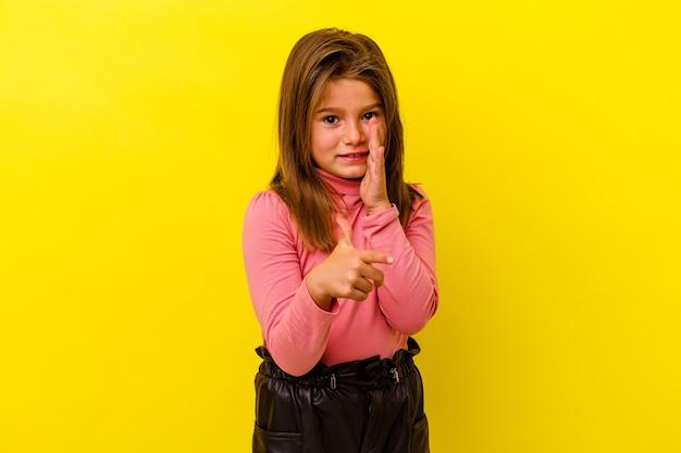 Bambina isolata sulla parete gialla che dice un pettegolezzo, indicando il lato che segnala qualcosa