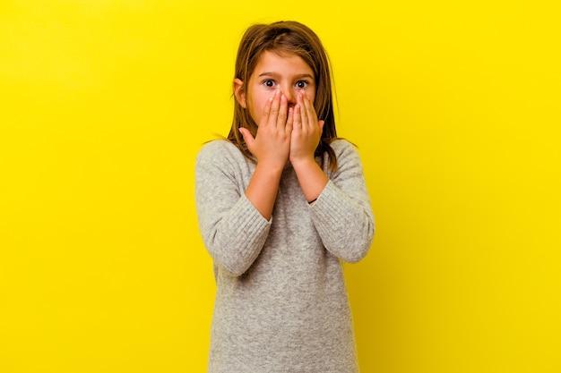 Bambina isolata sul muro giallo scioccata, che copre la bocca con le mani, ansiosa di scoprire qualcosa di nuovo