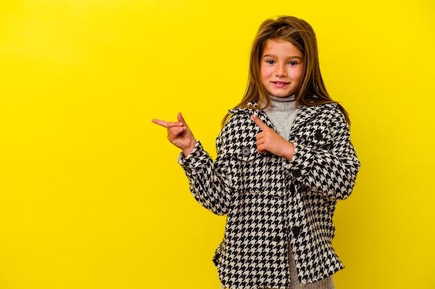 Bambina isolata sulla parete gialla scioccata che punta con il dito indice a uno spazio di copia