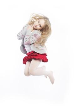 La bambina salta su uno sfondo bianco