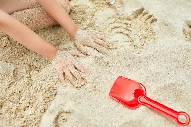 Bambina che si diverte sulla spiaggia e gioca con i giocattoli di sabbia, vacanze estive in famiglia