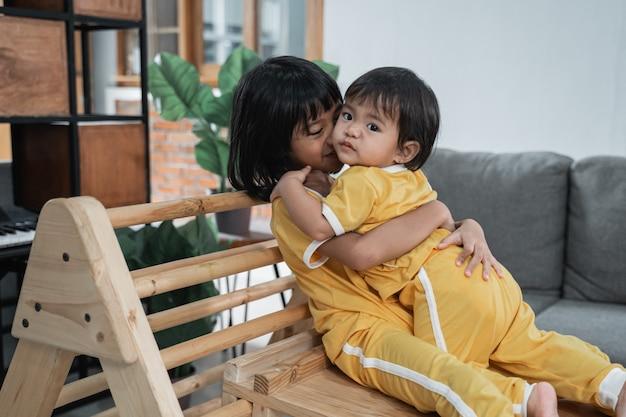 La bambina bacia la sua sorellina mentre si abbraccia seduta nei giocattoli del triangolo pikler in casa