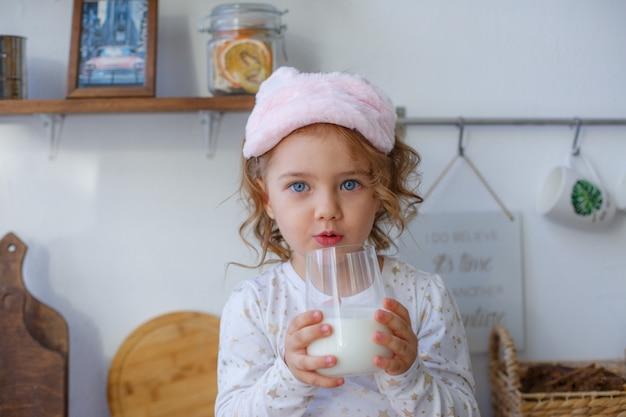 Bambina in cucina con in mano un bicchiere di latte dopo aver dormito, colazione