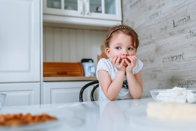 La bambina in cucina è seduta al tavolo ed è annoiata