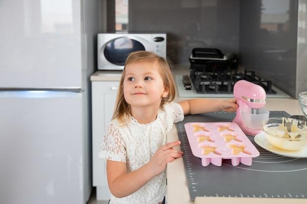 Bambina in cucina a preparare cupcakes