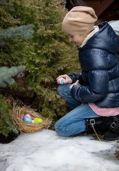 Bambina inginocchiata accanto all'albero e raccogliendo l'uovo di pasqua