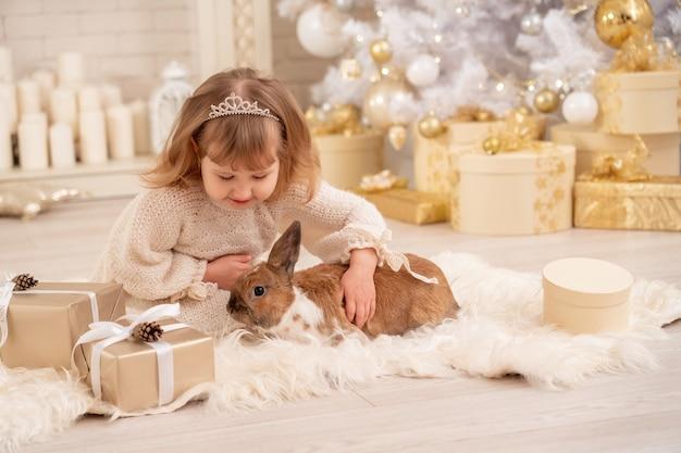 Bambina in vestito lavorato a maglia e diadema si siede vicino all'albero di natale bianco
