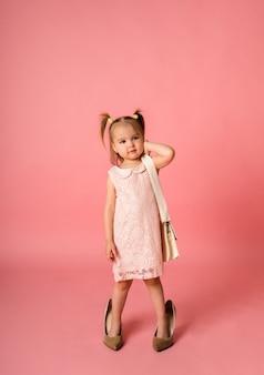 Una bambina in un abito di pizzo e scarpe su una superficie rosa con un posto per il testo
