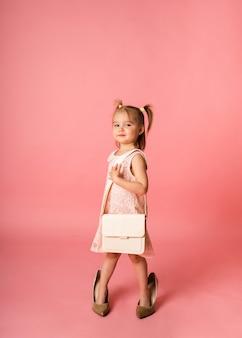 Una bambina in un abito di pizzo e scarpe con una borsa su una superficie rosa con un posto per il testo