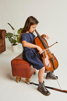 Bambina che impara a suonare il violoncello a casa