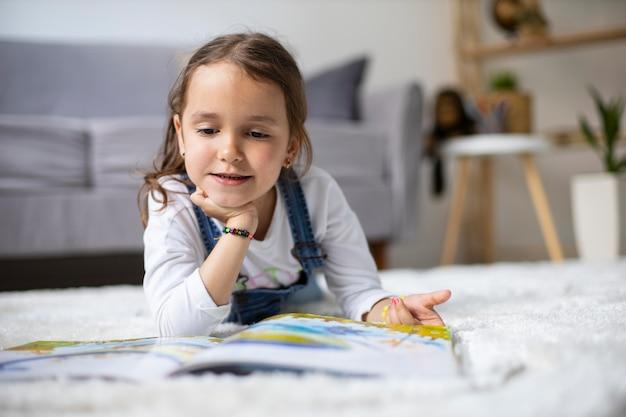 Bambina che impara a leggere da un libro