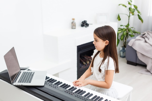 Bambina che impara il pianoforte durante la quarantena. concetto di coronavirus.