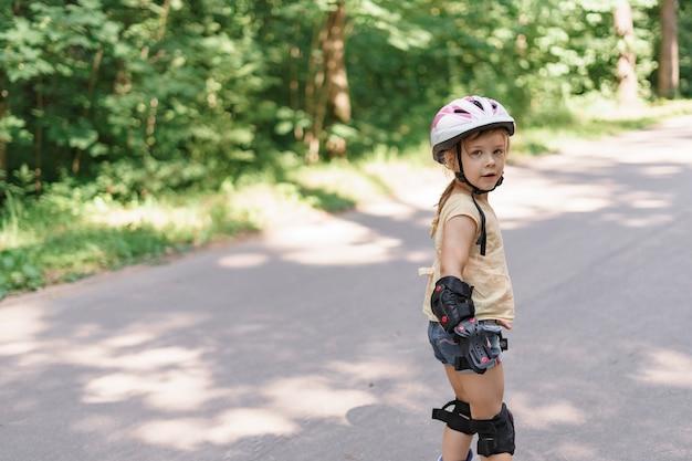 Bambina che impara a pattinare. bambino in abbigliamento sportivo protettivo