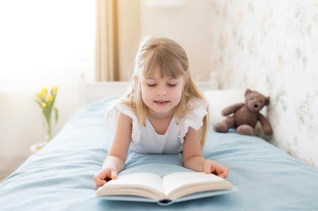 Una bambina si leva sul letto nell'elegante camera da letto e legge un libro blu, facendo i compiti. istruzione, concetto di istruzione domestica. tulipani gialli nel vaso vicino al letto
