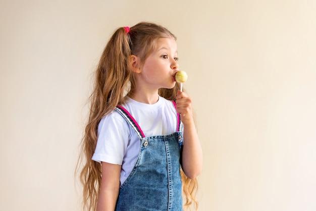 La bambina lecca il lecca-lecca.