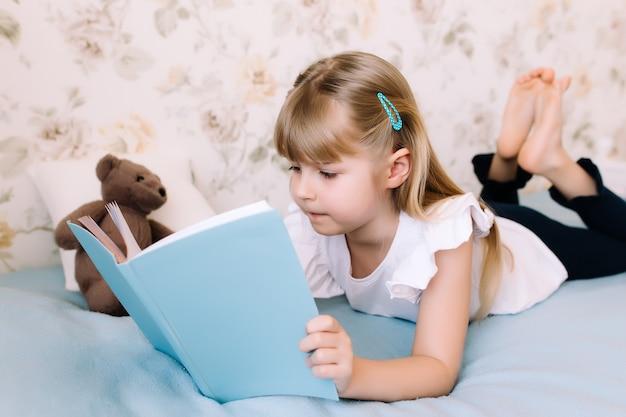 Una bambina giace sul letto in camera da letto e legge un libro blu. concetto di educazione. istruzione domiciliare. compiti a casa.