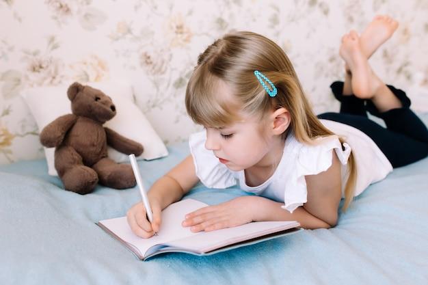 Una bambina giace sul letto in camera da letto e scrive in un libro blu. concetto di educazione. istruzione domiciliare. compiti a casa.
