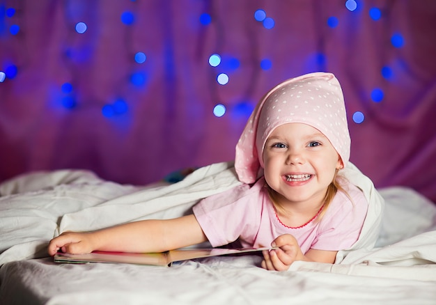 La bambina giace a letto in un berretto da notte con un libro per bambini e sorride