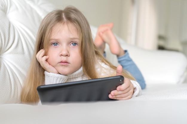 Una bambina si sdraia sul letto e gioca su tablet social internet.