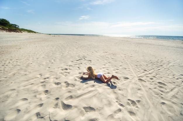 La bambina si trova a pancia in giù sulla spiaggia del mar baltico. curonian spit, lituania,