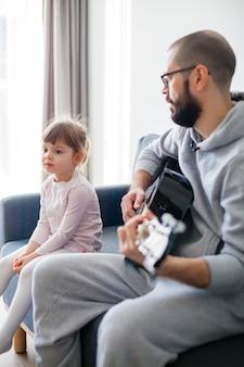 Bambina che ascolta suo padre che suona la chitarra per lei