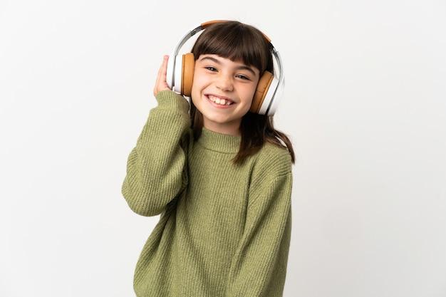 Bambina che ascolta musica con un cellulare isolato su sfondo bianco che ascolta musica