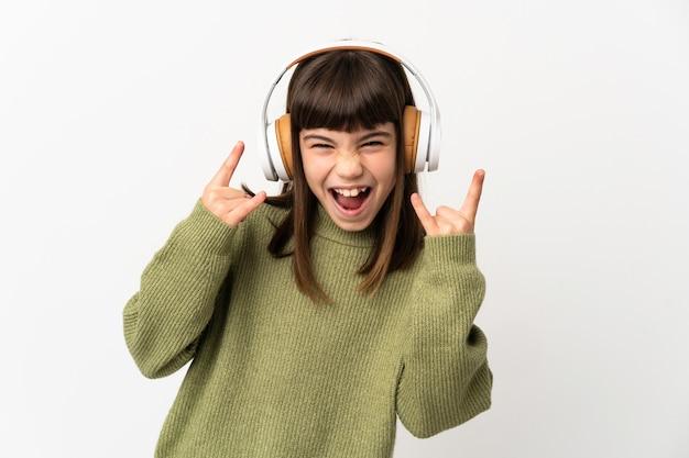 Bambina che ascolta la musica con un cellulare isolato sulla parete bianca che ascolta la musica che fa gesto di roccia
